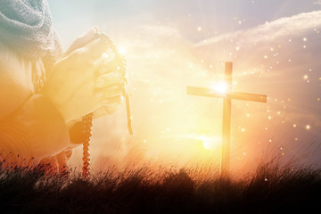 Fototapete - Double exposure. Woman with cross praying on nature sunset background, hope concept