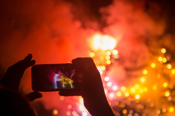 Hands hold a mobile phone and record ground fireworks
