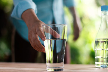 Woman's hand reaching for the glass of drinking water on wooden table, green nature background. Healthy concept.