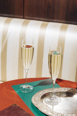 Two flutes of prosecco in an elegant bar with vintage pop colors