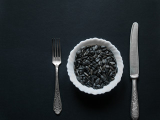 Sunflower seeds lie in a small round white cup on a dark background
