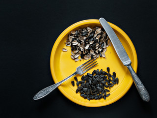 On a yellow plate lie the seeds of sunflower, husks from seeds, a knife and fork on a dark background
