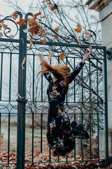 Mujer jugando con hojas de otoño retrato