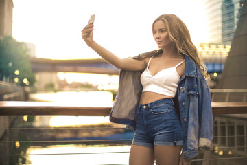 Beautiful woman taking a selfie on a bridge