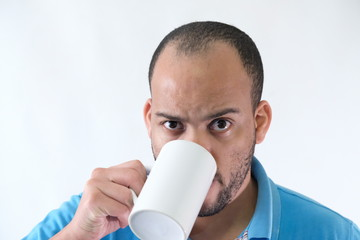 Man in blue t-shirt expressive face mug of coffee