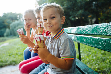 Happy children eating ice cream together outdoor. Photo of happy blond girls with two handsome boys sitting on the bench and smiling at camera.