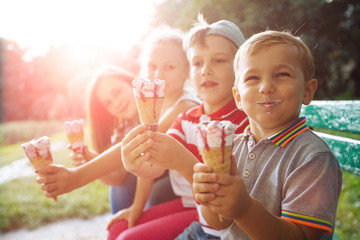 Group of four happy children eating ice cream together outdoor. Photo of happy blond girls with two handsome boys sitting on the bench and smiling at camera. Sun glare effect
