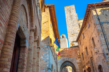 Panorama of buildings and towers in the old town of San Gimignano with the flags of Italy and the European Union. Italy, Tuscany.