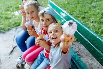 Group of four happy children eating ice cream together outdoor. Photo of happy blond girls with two handsome boys sitting on the bench and smiling at camera.