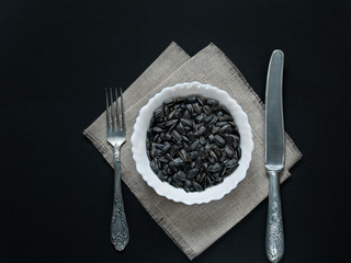 On a lianna napkin there is a dish with sunflower seeds and a knife with a fork next to a dark background