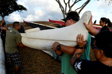 Members of the Alapahoe outrigger canoe club move their canoes off the beach to higher ground as Hurricane Lane approaches Honolulu