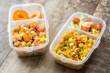 Lunch box with healthy food ready to eat on wooden table.