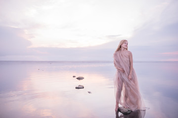 A girl in a weightless light fabric of pastel tones in the water of a calm pond with a reflection of the sunset gentle sky in the water. Artistic image of a gentle girl in nature.