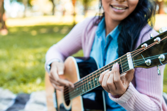 cropped image of african american woman playing acoustic guitar in park