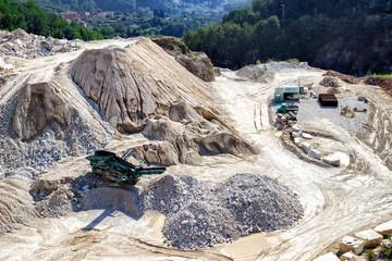 Excavator machine works with marble stones in Apennines mountains, Tuscany, near Carrara, Italy