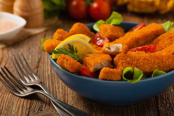 Fish sticks with salad in blue bowl.