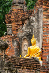 Beuatiful golden Buddha Image in front of old pagoda