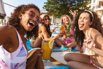 Group of women friends sitting outdoors in pool dressed in swimwears take a selfie by camera.