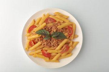 Pasta Fettuccine Bolognese with tomato sauce and basil in white dish on the white background.