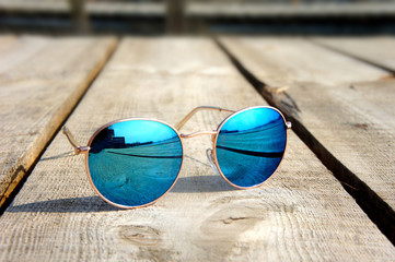 glasses with blue glasses on the sun lie on a wooden floor rest trip reflected in a glass... Wall mural