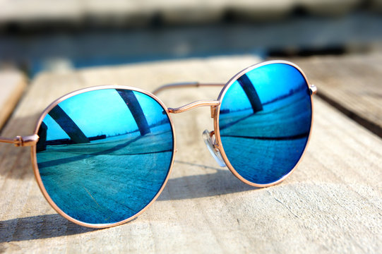 glasses with blue glasses on the sun lie on a wooden floor rest trip reflected in a glass...