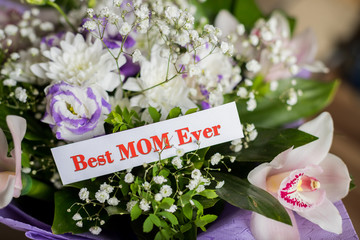 Happy Mother's Day gift, and Best Mom Ever greeting card on table.Beautiful big bouquet with orchids flowers and lisianthus. mothers day. Natural flowers. Floral gift. Romantic love design.