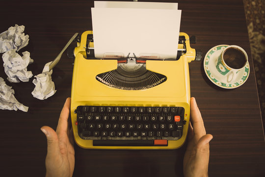 The writer sits in front of an old yellow typewriter, waiting for writing inspiration to appear.