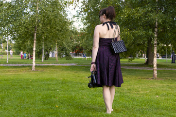 Portrait of a seductive young brunette in high heels smiling, walking barefoot on fresh grass in a sunny spring park, in a stylish black dress