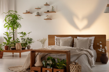 Shadow on the wall behind bed with wooden headboard in bedroom interior with plants. Real photo