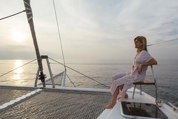 Mature woman on catamaran, watching sunset