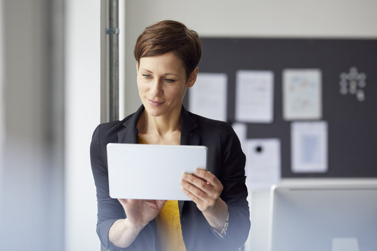 Attractive businesswoman standing in office, using digital tablet