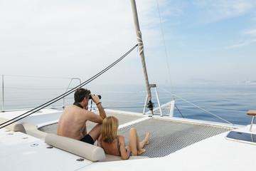 Mature couple sitting on catamaran trampoline, using binoculars