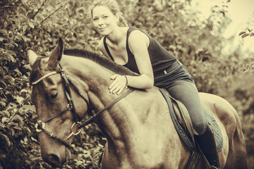 Young woman hugging and sitting on horse