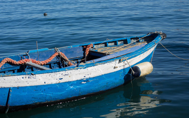 Blue and white boat in Procida, blue ocean, orange rope, sunny day