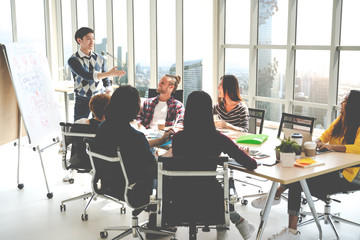 Young asian creative businessman standing and making presentation at modern office happy talking and brainstorming with teamwork on rear view and soft tone. Casual people business meeting concept.