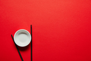 top view of arranged chopsticks and empty bowl on red backdrop