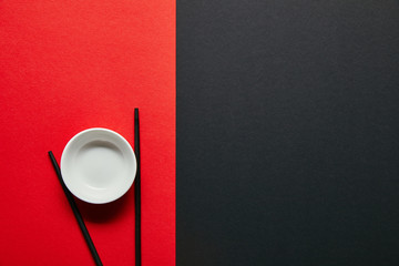 top view of arranged empty bowl and chopsticks on red and black background