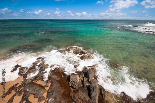 Waves crashing on the rocks on beach with crystal clear waters