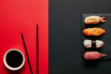 Fotobehang Sushi bar flat lay with soya sauce in bowl, chopsticks and nigiri sushi set on black slate plate on red and black background