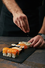 Aluminium Prints Sushi bar partial view of chef pouring sesame seeds on arranged sushi set on slate plate on dark tabletop