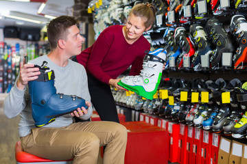 Woman seller is helping man to trying on ski boots