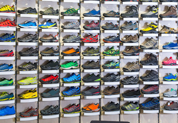 Image of big selection of sport shoes in market.