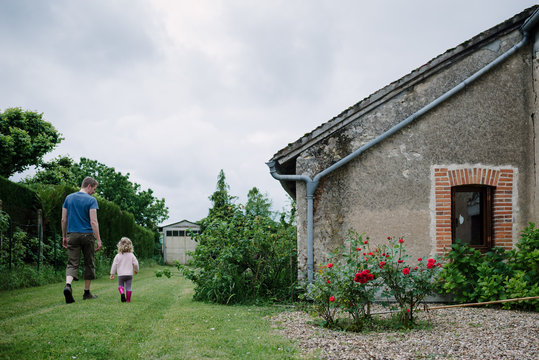 Father and daughter walking side by side in the garden of an old country side house