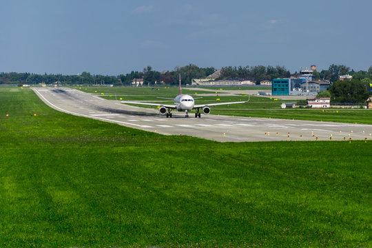 airplane on runway, green grass, blue sky