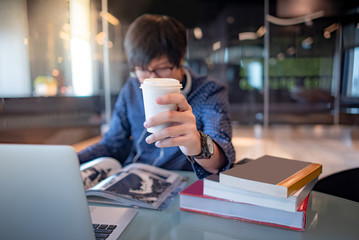 Young Asian man student reading book drinking hot coffee in public library. Education research and self learning in university life concepts