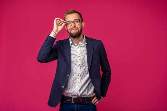 Portrait view of an attractive happy businessman with glasses on a pink background