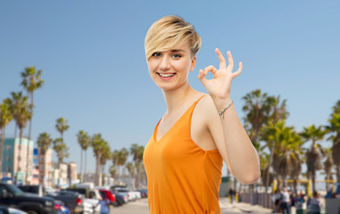 travel, tourism and summer holidays concept - happy smiling young woman showing ok hand sign over venice beach background in california