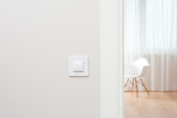 The wall switch is in the bright, contemporary interior. Open the door to the room. The chair by the window