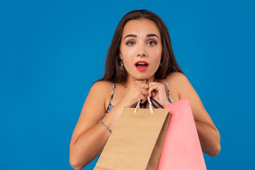 Beautiful young woman with shopping bags on the wonderful blue background