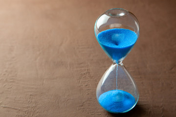 Hourglass with blue sand on brown background